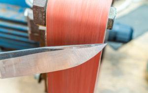 Grinding polishing sharpening knife blade on the belt grinder sander equipment