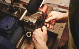Man sharpening a knife in the workshop