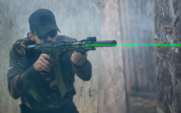 Army soldier in action aiming at weapon laser sight optics