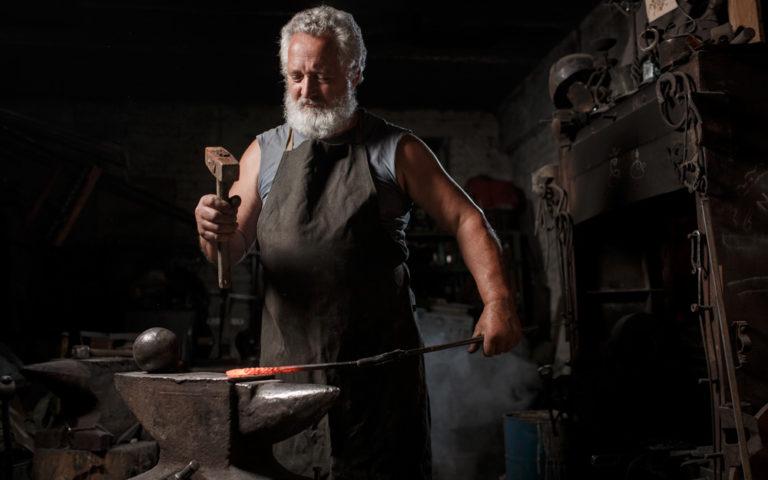 Blacksmith with brush handles molten metal