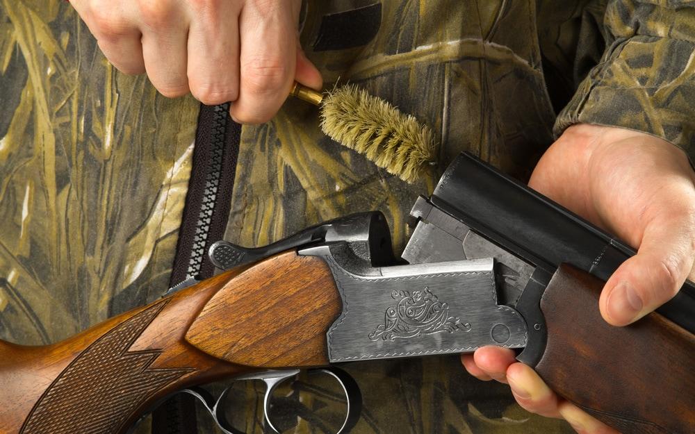 Hunter cleans the barrels of his shotgun