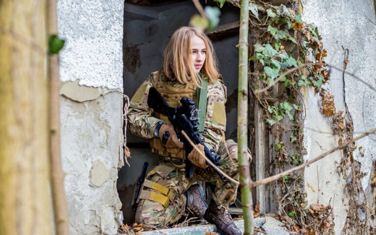 Beautiful girl in military uniform with an airsoft gun sitting on a window of an abandoned building