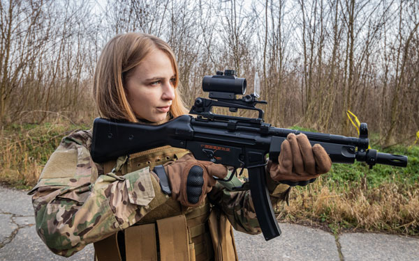 girl in military uniform with an airsoft gun standing on the road