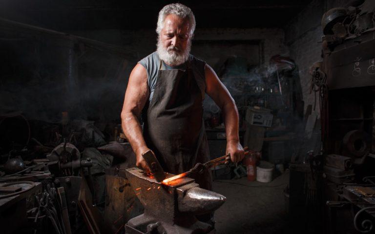 Blacksmith craftsman in apron works in blacksmith's shop