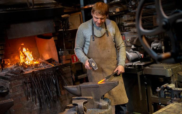 blacksmith manually forging the red-hot metal