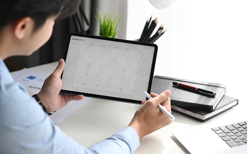 Businessman is looking at calendar with daily agenda on tablet