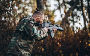 Camouflage soldier with Best Airsoft SMG and painted face playing airsoft outdoors in the forest