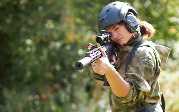 Sportive caucasian woman soldier shooting with rifle machine gun in the forest,