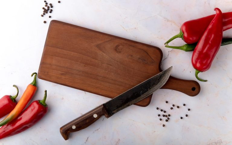 Top view of cutting board with knife and peppers and pepper spice