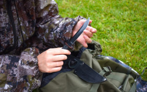 Tourist with a hunting sharp 1095 steel knife in hands outdoor