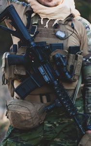 Airsoft military game player in camouflage uniform with armed assault rifle