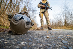 Airsoft helmet on the ground and a girl in military uniform in the background