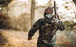 Camouflage soldier playing airsoft outdoors in the forest