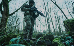Portrait of airsoft player in professional equipment with machine gun in the forest