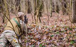 military uniform with an airsoft gun lying on the ground in the forest